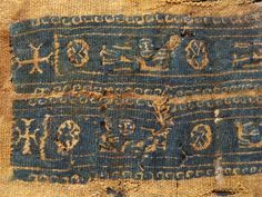 EGYPTIAN BLUE - Fragment of egyptian coptic funerary fabric with two stripes in blue, edged with a festoon, representing five elongated angels holding birds, separated by flowers, with four crosses patty on the edge. Coptic period, archaeology from the fourth - fifth centuries AD