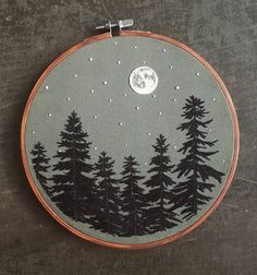 Embroidery Stitches Ideas Image of Tree Silhouette Embroidery Hoop - full moon, stars and black coniferous trees stitched onto dark sage fabric cinnamon colored hoop Hand Embroidery Stitches, Embroidery Hoop Art, Hand Embroidery Designs, Cross Stitch Embroidery, Cross Stitch Patterns, Embroidery Ideas, Hand Stitching, Embroidery Sampler, Simple Embroidery