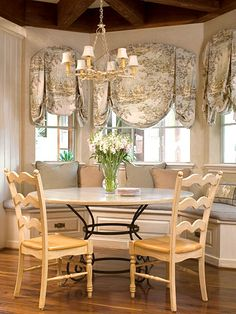 French Country style features toile, fresh flowers in clear glass vases, furniture with graceful lines, iron furniture, and heavy wooden beamed ceilings.