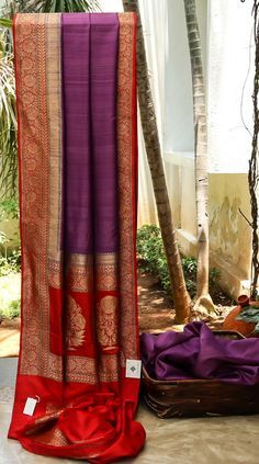 LOVELY PURPLE BENARES TUSSAR UPLIFTED BY A RED BORDER WITH AN INTRICATE GOLD WEAVE. THE UNUSUAL PALLU ADDS ANOTHER DIMENSION TO THE SAREE