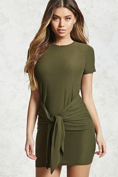 A bodycon dress constructed from a soft stretch knit featuring subtle ruched sides with a self-tie sash waist, short sleeves, and a round neckline.