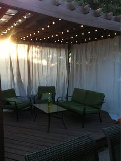 drop cloths as curtains, ikea dignitet curtain wire, frosted lights from target, citronella wine bottle. can't wait to put this space to use!