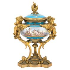 French Gilt-Bronze and Sevres Style Porcelain Urn  Late 19th century  Of classic form, with a loose domed cover and foliate finial, decorated along the center with a continuous landscape scene with putti, against a turquoise ground heightened with gilt and enamel, on three winged caryatids supports continuing to a triangular platform base