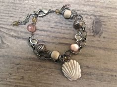 Fun, beach chic hand carved ox bone seashell amulet bracelet... Beach inspired bracelets are among my favorite jewelry pieces to make. The wooden beads, silver tone spacers, copper tone beads, pink acrylic beads and glass beads are a repurposed strand. I also added an antiqued brass chain, which makes it a double strand. An electroplated brass lobster claw clasp for closure.