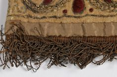 single buff leather glove, traditionally believed to have belonged to King Charles I, circa 1630-40. worked with delicate stylised honeysuckle motifs in wine silk and gold thread, the remains of looped gold thread strapwork, edged and part lined in pale brown silk, golden fringes to the gauntlet edge,