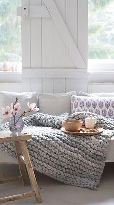 Frühlingshaftes, hyggeliges, skandinavisch angehauchtes Wohnzimmer mit Kuscheldecke
