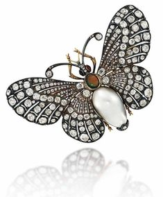 A LATE 19TH CENTURY BLACK OPAL, BLISTER PEARL AND DIAMOND BUTTERFLY BROOCH The head set with ruby cabochon eyes, to the black opal cabochon thorax and blister pearl body, between old-cut diamond-set wings, mounted in silver and gold, with en tremblant fitting to the reverse, circa 1890, 7.5cm wide by corrine