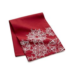 Continuous line snowflakes, embroidered in white, add a lyrical touch to this stylish red dishtowel.