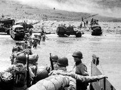 Mardi 6 juin, mi-journée - Les renforts continuent d'arriver à Omaha Beach. La progression des véhicules est rendue difficile. Six heures après la marée basse, la mer est au plus haut : les soldats arrivent sur un monticule de galets puis doivent franchir une zone de 200 mètres de marécages. Au loin, on aperçoit les hommes grimpant en file indienne le talus d'une cinquantaine de mètres de hauteur qui domine la plage.