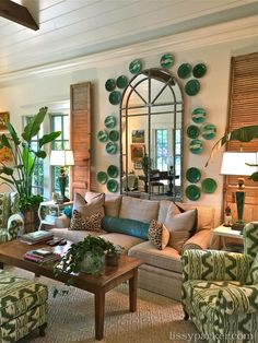 Majolica plates surround the mirror in a refreshing arrangement is frames by antique shutters.