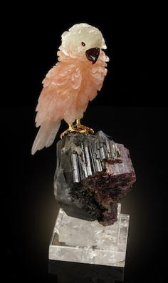 Pink Morganite and Green Beryl Carving of a Cockatoo on Watermelon Tourmaline Base  By Peter Mueller Brazil  A room-sized display piece, this composition incorporates a pink morganite-green beryl carving of prodigious size, weighing approximately 4146 carats, having excellent strength of color. With carnelian agate beak and cabochon rubellite tourmaline eyes. The gold vermeil feet rest upon a large specimen of watermelon tourmaline having a deep pink core. Raised on a polished rock crystal…