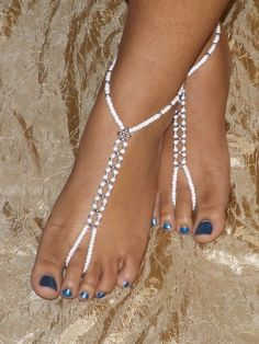 This pair of Barefoot sandals was made with stretch magic cord, porcelain white glass beads and silver tone beads.