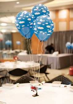 Centro de mesa: balões azuis decorados com nuvens.