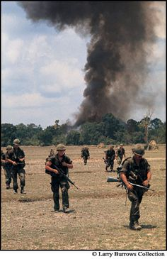 As Cobra gunships hit the village, Americans of the 25th Infantry Division move to a safer position.  Larry Burrows. May 6 1970. Ph Tasuos, Cambodia.