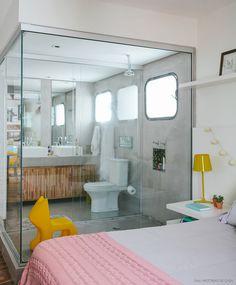 um banheiro totalmente aberto para o quarto, com parede de vidro e tudo