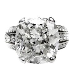 Unique Cushion Diamond Engagement Ring showcases a magnificent 10.73-carat, GIA-certified (GIA 16394978) cushion cut diamond (K color; VS2 clarity) in the center and 2.50 ctw of dazzling round diamonds on the sides.