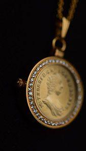 Hodinky s mincí od Národní Pokladnice. Vsazená mince je celá pozlacená 24karátovým zlatem. Pro impozantní dojem je obvod hodinek vykládán 45 zirkony.