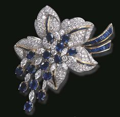 A SPECTACULAR SAPPHIRE AND DIAMOND FLORAL BROOCH, BY SABBADINI  Centrally set with a circular and marquise-cut diamond cluster pistil, enhanced by oval-cut sapphires, extending similarly-set articulated tassels, to the pavé-set diamond undulating petals, accented by calibré-cut sapphire veining and ribbon, mounted in platinum and 18k gold, in a Sabbadini green leather pouch Signed Sabbadini, Made in Italy