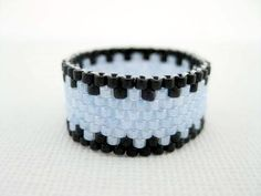 A beautiful peyote ring! Made of Japanese delica beads in black and pale blue pearl.  The ring is just over 3/8(1cm)wide. The size of the ring is up to you, it can be made in any size. It is lightweight and very comfortable to wear!  Check out my other beaded rings in many different colors, styles and designs: http://www.etsy.com/shop/MadeByKatarina?section_id=5864177  Please contact me if you have any questions.  Thank you for looking and have a nice day