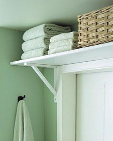 Put a shelf over bathroom door for extra storage. good idea.. cute too!