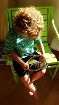 embroideryhoopweaving4 : a young boy weaving on an embroidery hoop using thick wool and a large needle. a beautiful and usefully craft for kids.