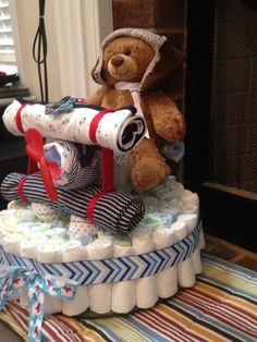Airplane diaper cake for baby shower. Contains: 2 bottles (cheap - not reusable), onesies, blankets, washcloths (wheels), spoon & fork (propellor), bear, aviator hat (Amazon), Popsicle sticks & ribbon