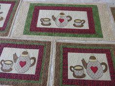 Conjunto de Cozinha feito em patchwork e aplica��es contendo: <br>01 caminho de mesa - 40cm x 90cm <br>04 pe�as de jogo americano - 35cm x 45cm <br> <br>Feito com tecidos nacionais e importados. 100�0algod�o.