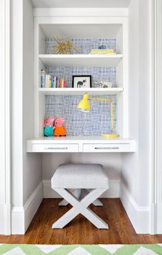 """The desk in this children's room has a small upholstered stool that can be swapped out for a larger seat as the child grows. The back of the built-in desk is a blue and white """"cheesecloth"""" pattern that breaks up the neutrals."""