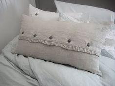 Lumbar pillow with button closure and ruffles.