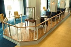 This interior lobby space uses a Keuka style cable railing to create the feeling of relaxing on a boat. Notice the curved railing post, teak and holly floor and the carpet colors simulating the beach and the water. Our railings can be custom made to work with any decor you would like to imagine.