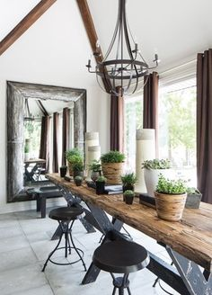 Rustic chic is the best way to describe this dining room. Stools are a stylish seating option to use w/ this table. The whole look is lit up perfectly w/ that chandelier!