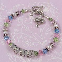 Child Name Bracelet - C03   A rainbow of Swarovski crystal colours – light rose, peridot, aquamarine and light amethyst – combined with white Swarovski pearls and Bali sterling silver. This image shows the C03 design with small classic toggle clasp and swirly heart charm – large letter blocks. Crystal colours – light rose, peridot, aquamarine and light amethyst. Pearl colour – white.