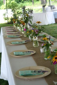 our table setting - wildflowers, bamboo plates, homemade cloth napkins, burlap runners w/ table numbers stenciled on end. love love love!