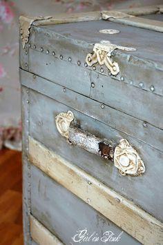Entire piece painted two coats of by Annie Sloan Chalk Paint in Paris Grey and the wood slats with Old Ochre and metal hardware in Old White. Via old trunk makeover - One Girl In Pink