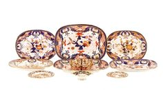 """Royal Crown Derby (English, founded 1750), late 18th-20th century. A group of 10 assorted porcelain dishes, including 6 platters in varying sizes, a candy dish, a footed dish, and two saucers, each hand enameled with a red and cobalt Imari pattern with gilt accents. Most marked to underside. Approximate height (of largest platter) 1.375"""", width 13.25"""", depth 10""""."""