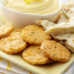 """Cheesy Chive Crisps Recipe -""""These snack bites are great to keep on hand for guests,"""" says Eve McNew of St. Louis, Missouri. Since the recipe makes a lot, you might want to freeze some of the cheese logs for future use. Be sure to thaw them in the refrigerator for 2 to 3 hours before slicing and baking."""