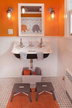 Orange and gray boy's bathroom features top half of walls painted bright orange and bottom half of walls clad in white staggered tiles lined with a Kohler Brockway Sink fitted with two gooseneck faucets and a white beveled mirror lit by cage sconces as well a pair of gray step stools placed atop of an orange bath mat layered over a marble basketweave marble floor.