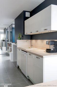 Projet : Les clients souhaitaient ouvrir la cuisine sur l'entrée de l'appartement. Un espace bureau a été conçu dans un cagibi existant. L'idée était de travailler avec des camaïeux de gris en adéquation avec un sol en grès cérame pour apporter un côté moderne à l'espace. La cuisine en laqué blanche et bois clair se veut fonctionnelle et contraste avec les murs gris anthracite. - Côté Maison Projets