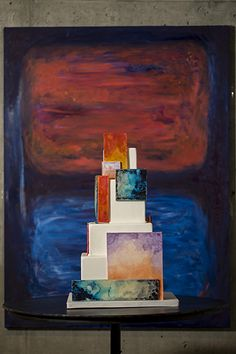 This magnificent cake truly is art. Square and rectangle accents in intricate watercolors offset four square tiers for an abstract look that perfectly mirrors the painting behind it.