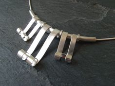 """""""Scroll"""" necklace with free-moving scrolls, in sterling silver with snake chain, by Silver Fox Jewellery."""