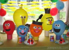 Sesame Street Balloons- Tape on paper faces. Cut fringe for Bert & Ernie's hair & Big Bird's feathers.  Tape balloons to food cans wrapped in paper so they won't tip over.