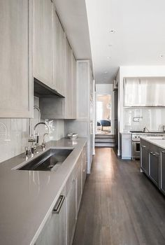 Contemporary kitchen features gray stained cabinets paired with gray quartz countertops and a lighter gray quartz backsplash, A wide stainless steel kitchen sink and a pull out faucet stands under cabinets.