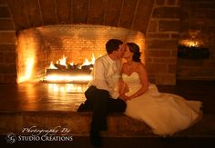 Bride and groom kissing by fire. Photo by Michael Gianechini