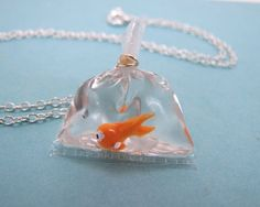 A tiny orange goldfish floats in a plastic bag filled with water (which is really just clear gel). The little bag is even tightly tied with a rubber band just like real ones! Brings back fond memories of winning goldfish at the fair.