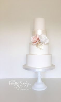 Soft pearl lustre wedding cake with peach and white statement flowers and gold leaves