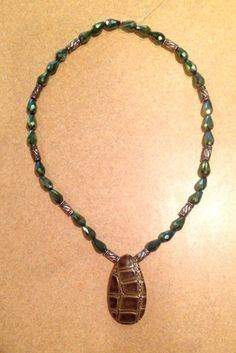Hand made necklace inspired by the green reptile charm in the middle, It is made with love and lots of care. It hangs about 18 inches. Jewelry is a passion of mine and i hope this little gem or one like it can end up in your loving home.