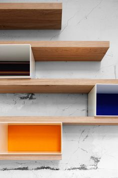 "From Studio Segers, a modular shelving system with ""sober finishes and colourful upholstered back wall sections for contrast."""