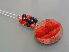 Makowa panienka - Nowość!  Uroczy wisior z kwiatem maku - po jednej stronie jest on lekko pochylony, po drugiej - z rozchylonymi płatkami. Wisior w technice decoupage, z czerwonymi spękaniami na grafitowoszarym tle. Lakierowany. Ozdobiony szklanymi koralami w kolorze ciemnego grafitu i koralowymi jadeitami. Zawieszony na długim posrebrzanym łańcuszku. Średnica zawieszki to 6cm.