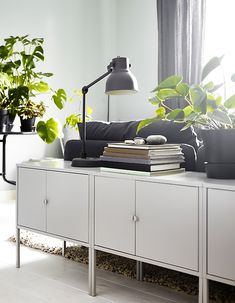With a mix of modern furniture and closed and open storage your living room feels balanced. Put a couple of modern cabinets behind the sofa so they blend in with the interior. IKEA has a lot of cabinets such as LIXHULT cabinet in metal/grey.