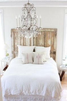 Wood headboard with light bedding and chandelier for guest bedroom